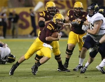 Arizona State quarterback Taylor Kelly, left, runs for a first down against the Northern Arizona defense during the first half of their NCAA college football game on Thursday, Aug. 30, 2012, in Tempe, Ariz. By Catherine Holland