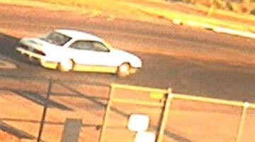 The suspect vehicle is a Buick or Mercury four-door sedan with white and tan paint. By Jennifer Thomas