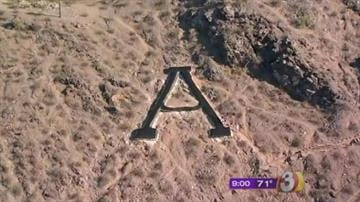 Hours after Arizona State University's A on A Mountain was painted green -- presumably by fans of the Oregon Ducks -- students hustled up the butte and repainted it black. By Catherine Holland