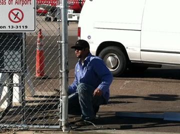 A repair man looks at the damaged fence. By Catherine Holland