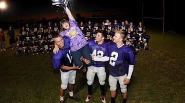 """Sophomore Chy Johnson with Carson Jones (left) and the rest of her """"boys,"""" the Queen Creek, Ariz., high school football team. By Catherine Holland"""