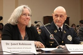 Chasta, Minn., Police Chief Scott Knight looks on as Emily Nottingham testifies to a panel of House Democrats considering action to curb gun violence. Nottingham's son, Gabe Zimmerman, was killed in a 2011 mass shooting in Tucson. By Connor Radnovich