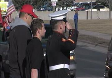 Marine Cpl. Phillip Scavo (saluting) and Alex Davenport (middle) watched the procession for Staff Sgt. Jonathan D. Davis. By Jennifer Thomas