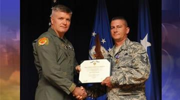Brig. Gen. JD Harris (left), former 56th Fighter Wing commander, presents a Purple Heart Medal June 29, 2012, to Master Sgt. Iordanis Velissariou. By Jennifer Thomas