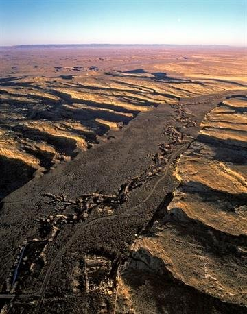 Oblique aerial view of the central-western portion of Chaco Canyon, with Pueblo Bonito at bottom center. Pueblo del Arroyo is along the watercourse immediately above it. View is to the west, with the Chuska Mountains on the horizon. By Adriel Heisey