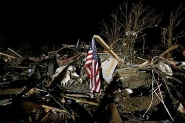 A flag flies in the debris of a mobile home after a tornado struck a mobile home park near Dale, Okla., Sunday, May 19, 2013. (AP Photo Sue Ogrocki) By Sue Ogrocki
