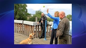 Former U.S. Rep. Gabrielle Giffords, D-Ariz., tosses a ball for her 2-year-old dog, Nelson, with husband, former astronaut Mark Kelly, at an overlook of Cook Inlet in Resolution Park on Tuesday, July 2, 2013, in Anchorage, Alaska. By Jennifer Thomas