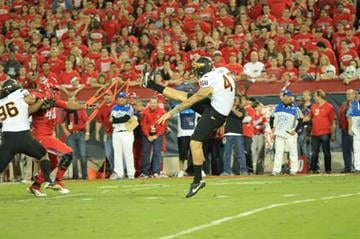 Josh Hubner let's off a booming punt in last year's Duel in the Desert game against the Arizona Wildcats. By Brad Denny