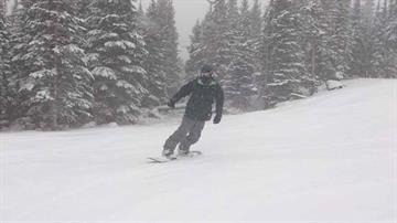 A snowboarder enjoys the fresh powder at Sunrise Park Resort By Christina O'Haver