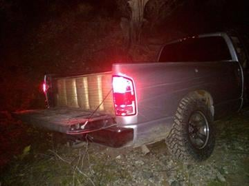 Rear view of the Dodge truck used as a load vehicle, seen here abandoned in a wash. Bundles of marijuana are visible in the bed of the truck. By Jennifer Thomas