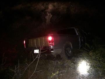 The load vehicle is at an extreme angle in the wash. Bundles of narcotics are visible in the truck. By Jennifer Thomas