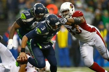 SEATTLE - DECEMBER 22:  Russell Wilson #3 of the Seattle Seahawks is pressured by Calais Campbell #93 of the Arizona Cardinals on December 22, 2013 at CenturyLink Field in Seattle, Washington.  (Photo by Jonathan Ferrey/Getty Images) By Jonathan Ferrey