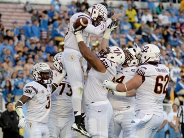 Jamil Douglas (74) lifts up quarterback Taylor Kelly after Kelly's TD run vs. UCLA By Harry How