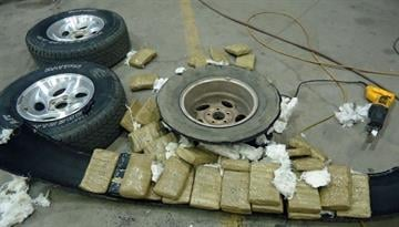 Packages of marijuana are removed from within the tires of a smuggling vehicle by CBP officers assigned to the Port of Douglas. By Jennifer Thomas
