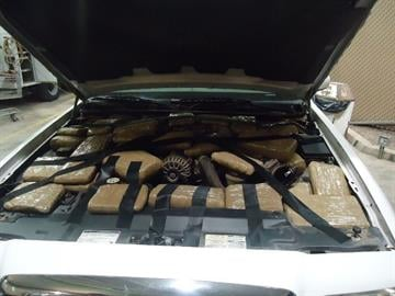 Packages of marijuana are located underneath the hood of a smuggling vehicle by CBP officers in Douglas, Ariz. By Jennifer Thomas