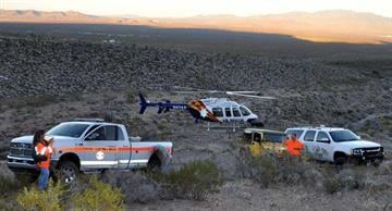 MCSO Search & Rescue members take cover behind GVFD unit as DPS Ranger takes off. By Jennifer Thomas