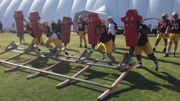 The ASU offensive linemen hit the sled. By Brad Denny