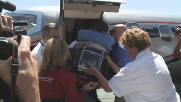 Amy Van Dyken-Rouen is loaded onto a plane. By Jennifer Thomas