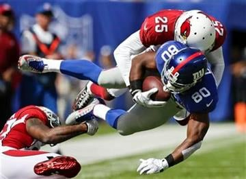 Arizona Cardinals cornerback Jerraud Powers (25) tackles New York Giants wide receiver Victor Cruz (80) during the first half of an NFL football game Sunday, Sept. 14, 2014, in East Rutherford, N.J.  (AP Photo/Kathy Willens) By Kathy Willens