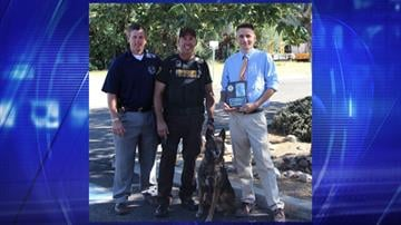 From left, K-9 Lt. Dan Raiss and Deputy Randy Evers presented Dr. Brice Smith with a plaque expressing immense gratitude for his efforts in helping Neo. By Jennifer Thomas