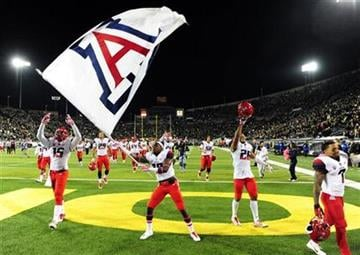 Arizona players celebrate after beating Oregon in the NCAA college football game at Autzen Stadium on Thursday, Oct. 2, 2014, in Eugene, Ore. Arizona won the game 31-24.(AP Photo/Steve Dykes) By STEVE DYKES