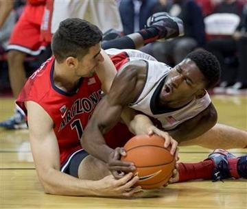 Arizona center Dusan Ristic, left, and UNLV center Goodluck Okonoboh fight for the ball during the first half of an NCAA college basketball game Tuesday, Dec. 23, 2014, in Las Vegas.  (AP Photo/Eric Jamison) By Eric Jamison