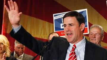 FILE - In this Nov. 4, 2014, file photo, Doug Ducey, who was elected as Arizona governor, waves to supporters on election night in Phoenix. Ducey will be inaugurated on Monday, Jan. 5, 2015, By Mike Gertzman