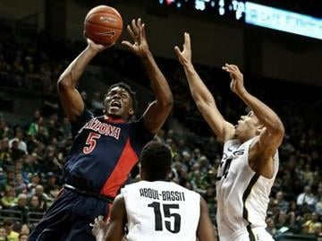 Arizona forward Stanley Johnson shoots over Oregon guard Jalil Abdul-Bassit, center, and forward Dillon Brooks, right, during the first half of an NCAA college basketball game Thursday, Jan. 8, 2015, in Eugene, Ore. (AP Photo/Ryan Kang) By Ryan Kang