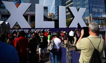PHOENIX, AZ - JANUARY 28:  People walk past the logo for the upcoming Super Bowl XLIX between the Seattle Seahawks and New England Patriots in an NFL fan on January 28, 2015 in Phoenix, Arizona.  (Photo by Justin Heiman/Getty Images) By Justin Heiman