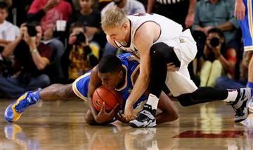 UCLA's Kevon Looney, bottom,  battles Arizona State's Jonathan Gilling for the ball during the first half of an NCAA college basketball game, Wednesday, Feb. 18, 2015, in Tempe, Ariz. (AP Photo/Matt York) By Matt York