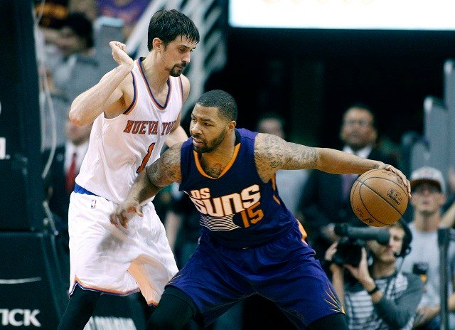 Phoenix Suns' Marcus Morris (15) leans into New York Knicks' Alexey Shved, of Russia, as he dribbles under the basket during the first half of an NBA basketball game, Sunday, March 15, 2015 in Phoenix. The Suns defeated the Knicks 102-89. (AP Photo/Ralph