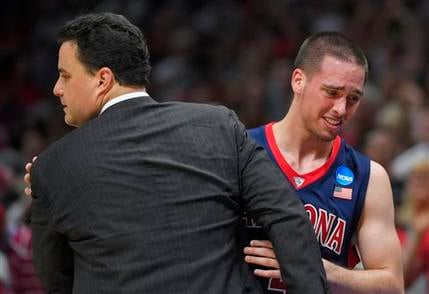 Arizona guard T.J. McConnell hugs head coach Sean Miller as McConnell leaves the game (AP Photo/Mark J. Terrill)