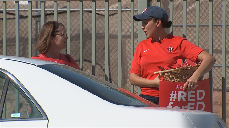 On Monday, several moms passed out red lollipops with red flyers at Hopi Elementary, encouraging other parents to join this week's walk-ins. (Source: 3TV/CBS 5)