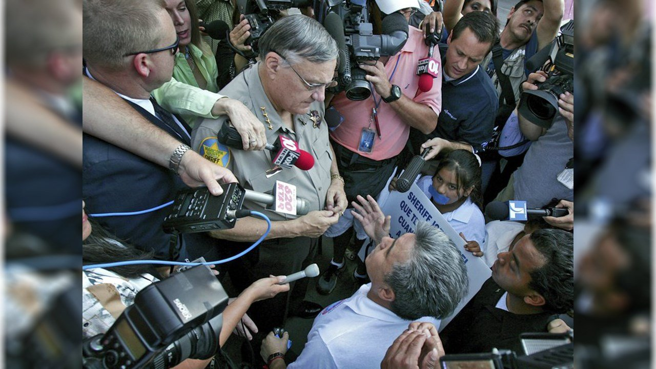 In this July 14, 2006, file photo, Elias Bermudez kneels before then-Sheriff Joe Arpaio at a protest over the lawman's immigration crackdowns. (Source: AP Photo/Matt York,File)